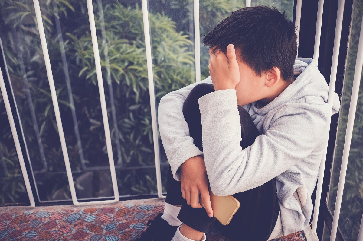 Young Asian preteen teenager boy hugging his knee and cover his